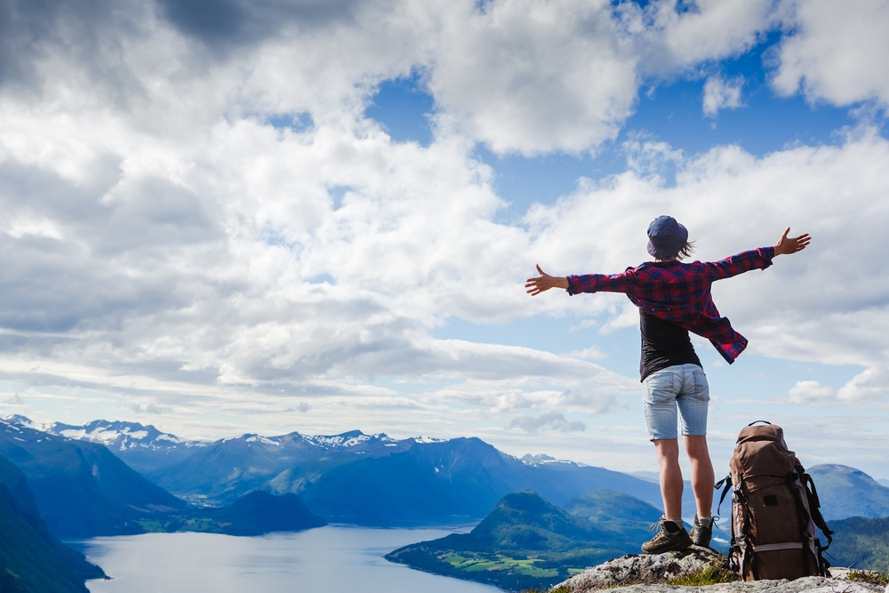 Girl standing on mountaintop with arms wide open
